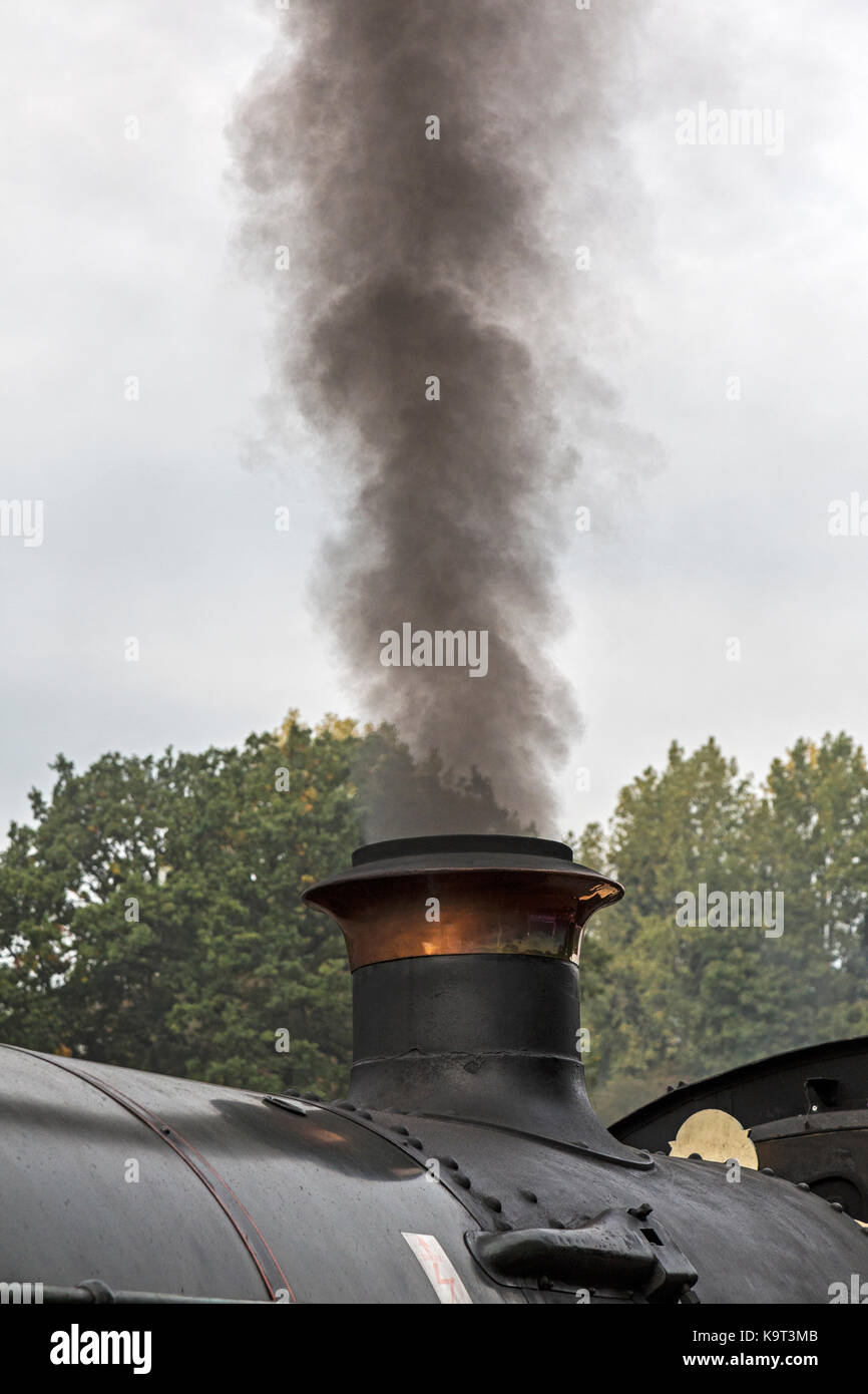 Steam and soot rising from the chimney of a steam locomotive train. - Stock Image