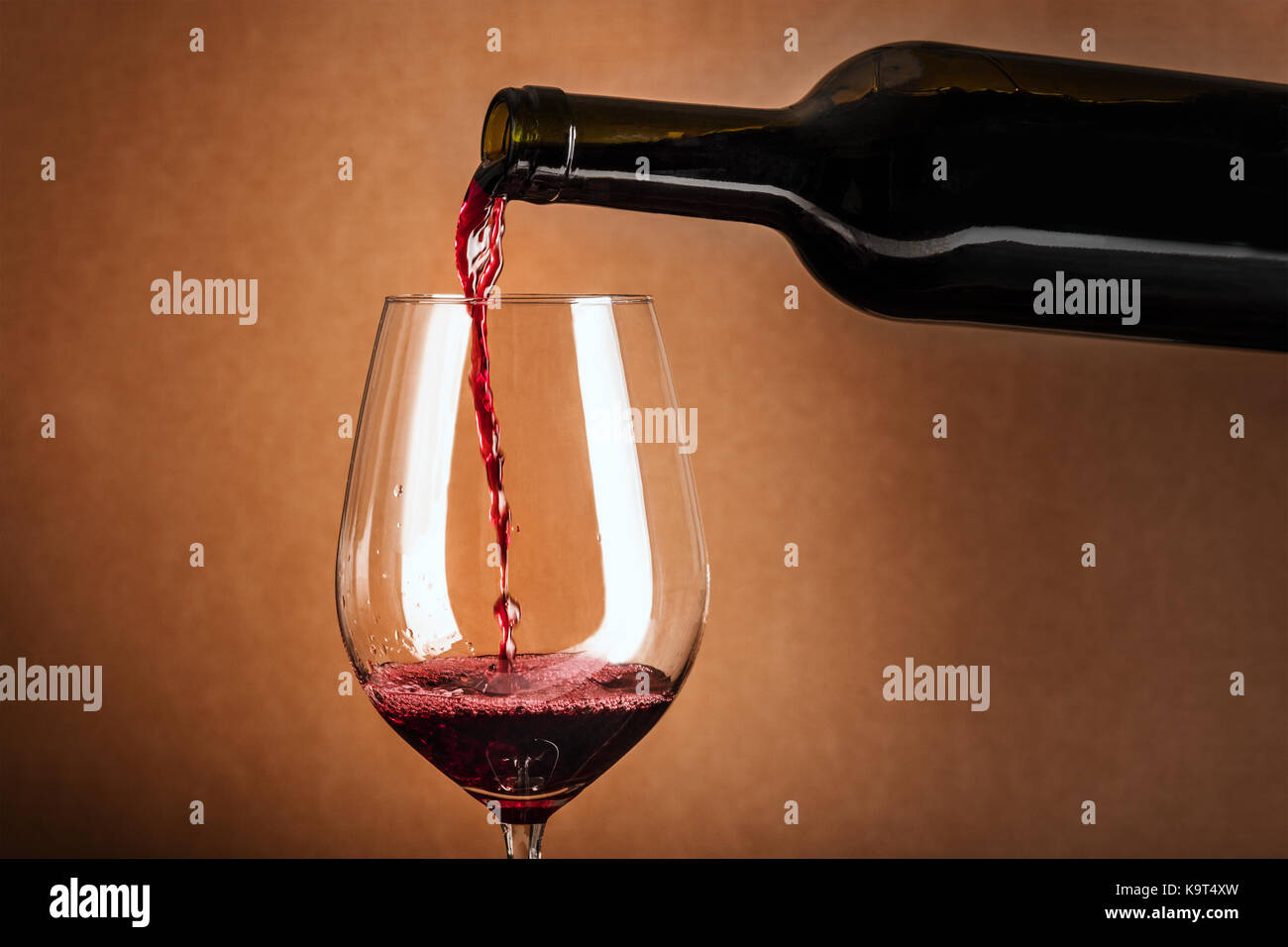 Red wine poured into glass from bottle - Stock Image