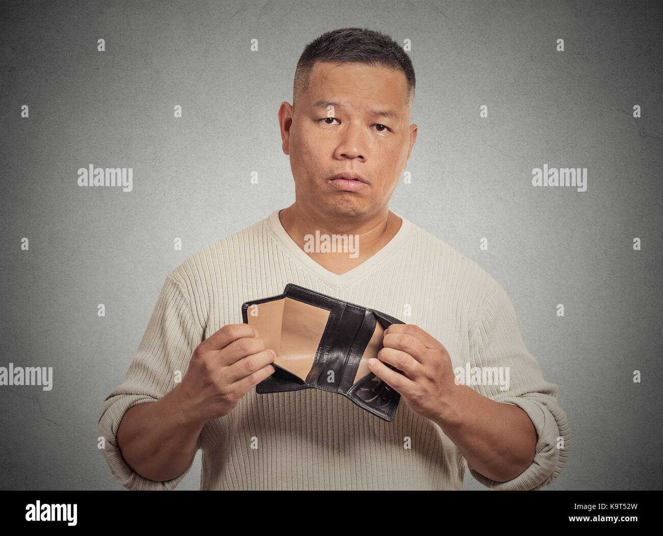 Closeup portrait stressed, upset, sad, unhappy middle aged  man standing with, holding empty wallet isolated grey - Stock Image