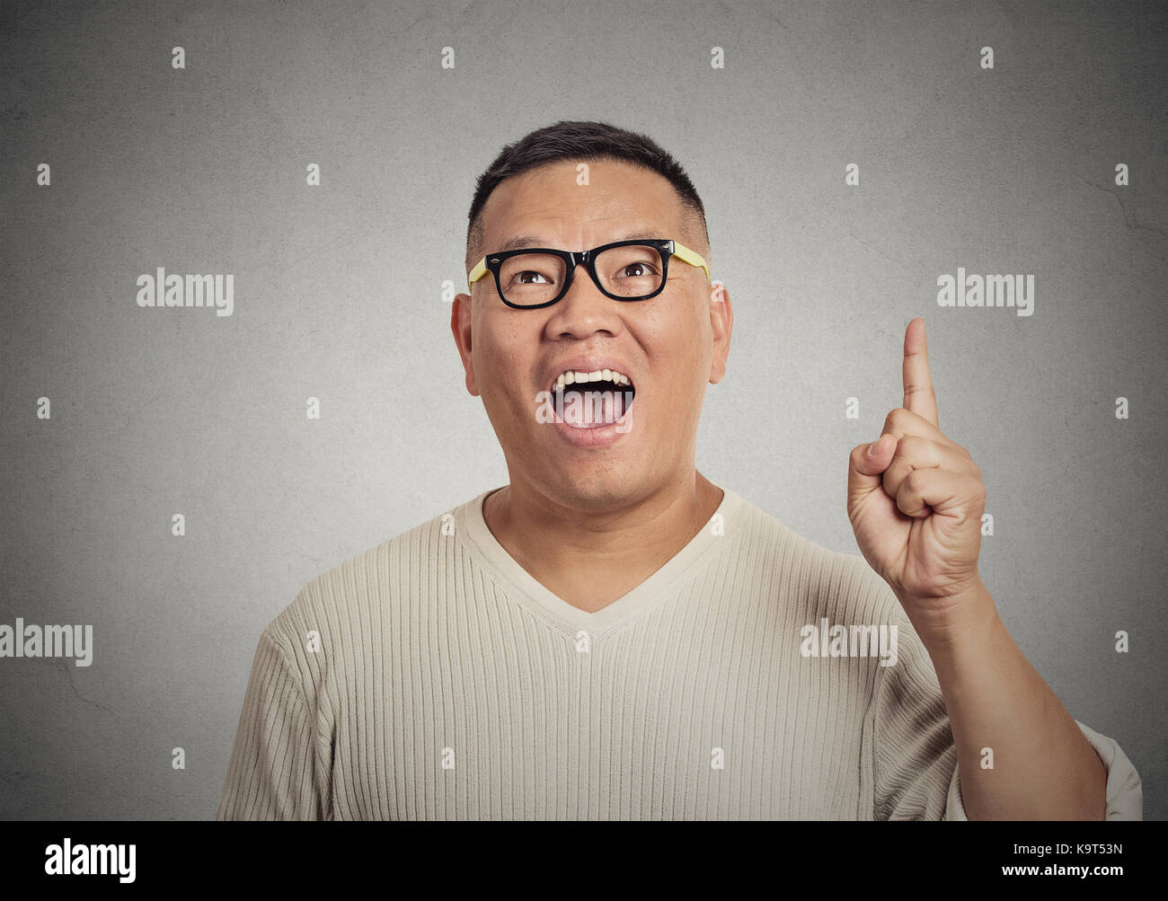 Portrait young man has an idea, pointing with finger up isolated on grey wall background. Excited guy with solution - Stock Image