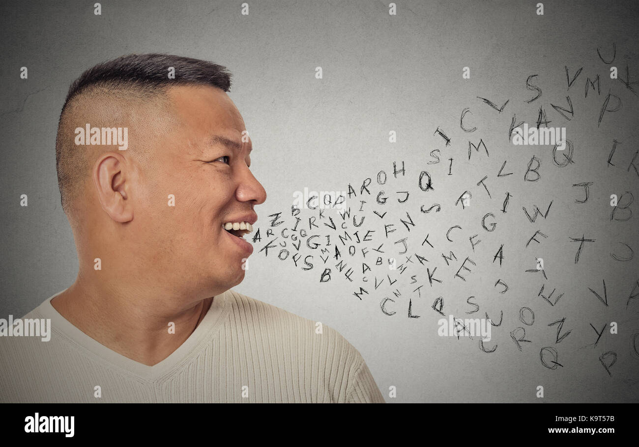 Side view portrait young handsome man talking with alphabet letters coming out of open mouth isolated grey wall - Stock Image