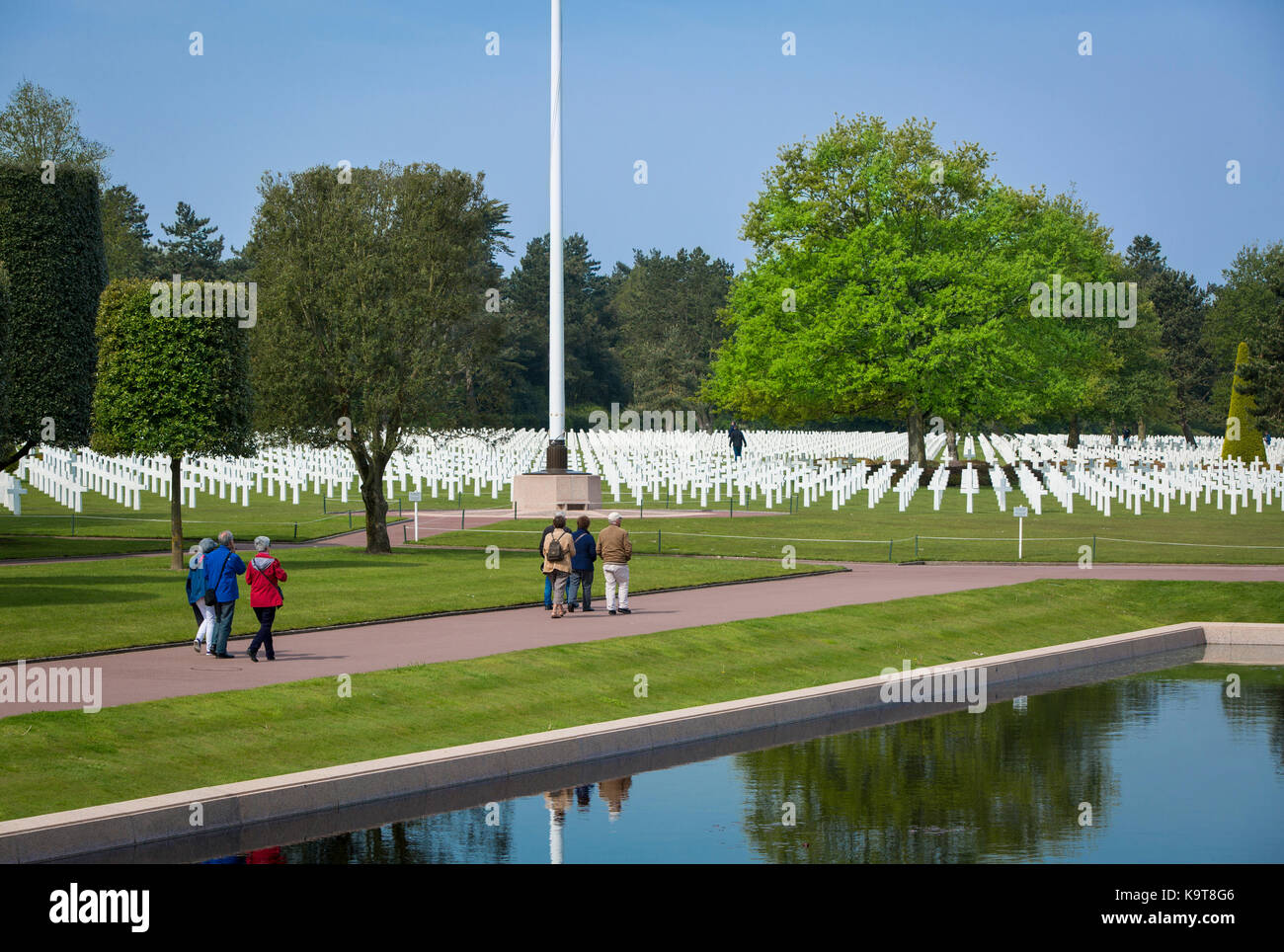 Visitors walk through the perfectly manicured garden and lines of crosses at the American Cemetery, Colleville-sur Stock Photo