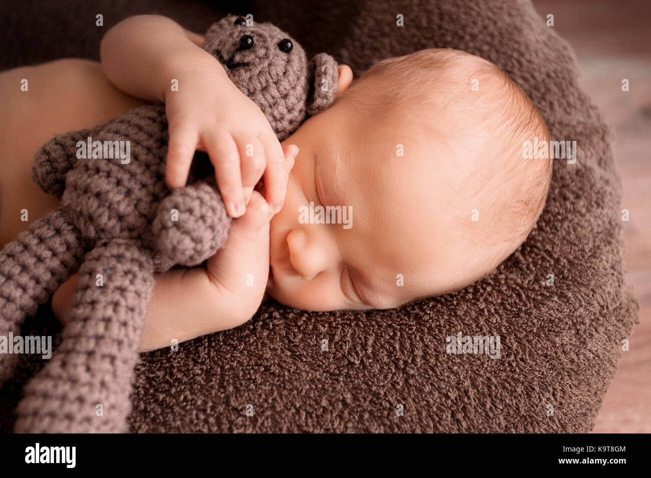 Newborn baby sleeping in a beautiful pose with a little bear - Stock Image