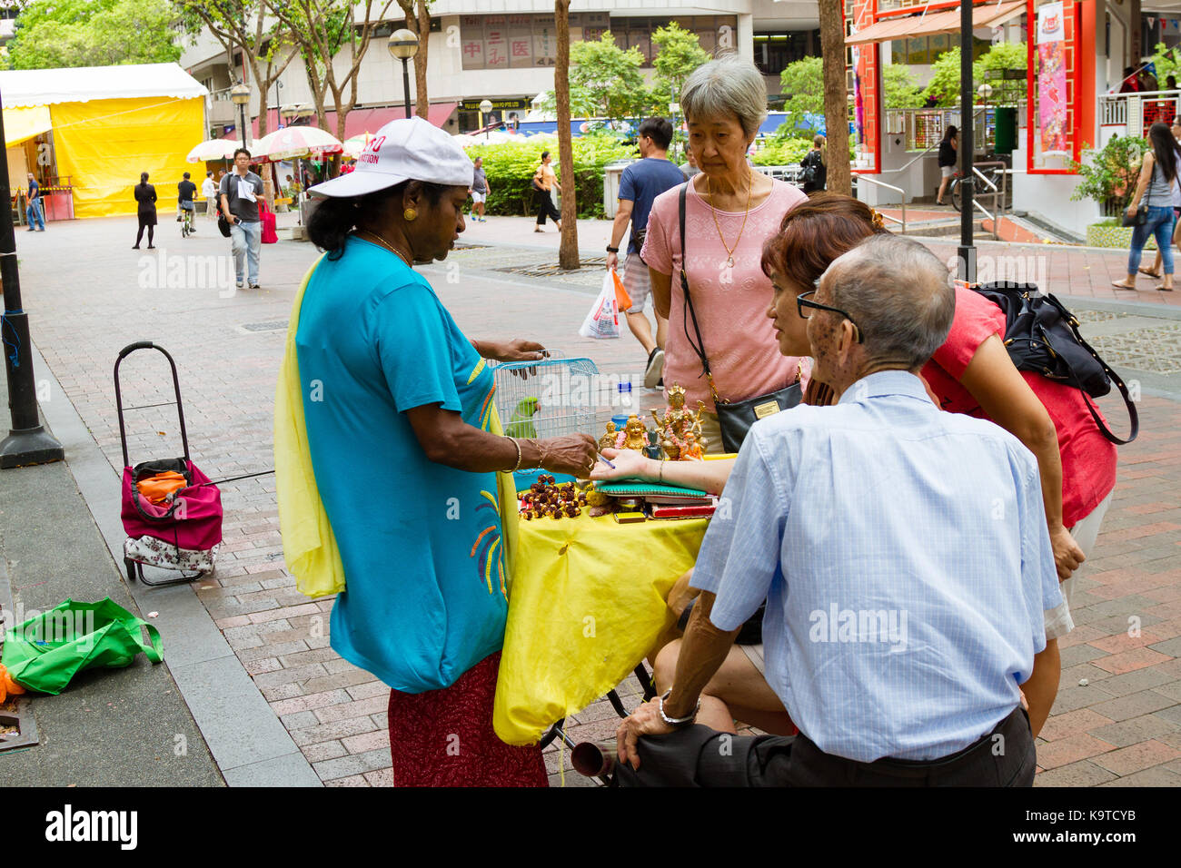 SINGAPORE - SEPTEMBER 7, 2017: A fortune teller practices chiromancy by reading the palm of a devotee outside the - Stock Image