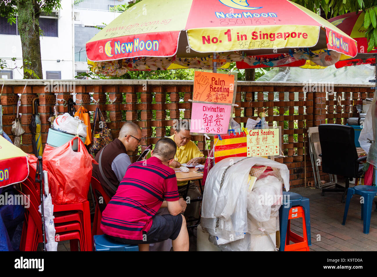SINGAPORE - SEPTEMBER 7, 2017: A fortune teller practices divination for devotees outside the Kwan Im Thong Hood Stock Photo