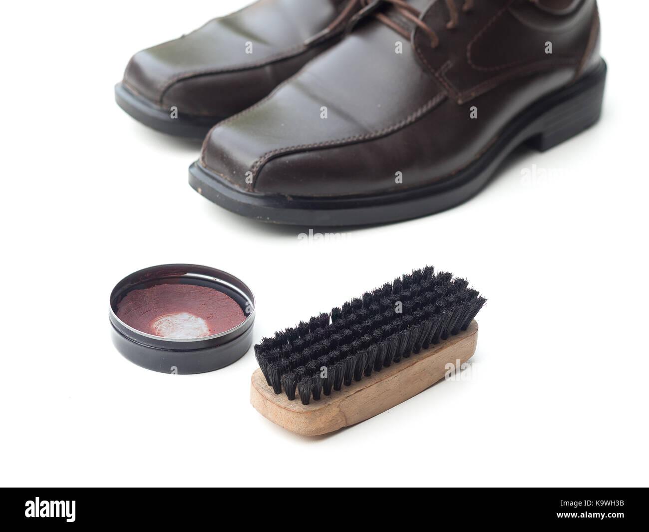 Dark brown shoe with shoe polish and brush shoe isolated on white background - Stock Image