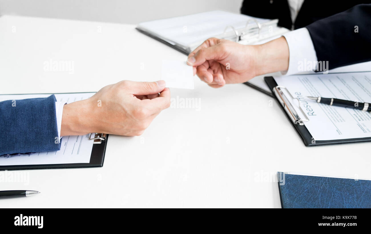 young businessman at the hiring interview in the office, meeting at office lobby, changing business cards - Stock Image