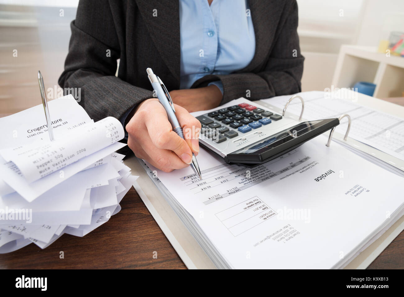 Close-up Of Businessperson Calculating Bills At Desk - Stock Image