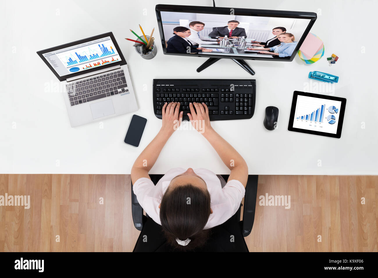 Young Businesswoman Videoconferencing With Co-workers On Computers At Desk - Stock Image