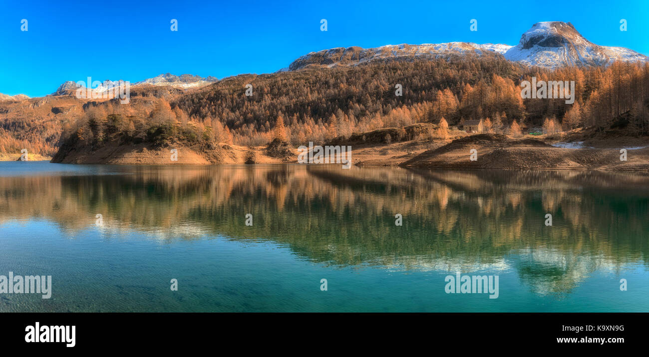 Lake of Devero in autumn season with high contrast, shadow and sunny lights with snowy mountains and blue sky in - Stock Image