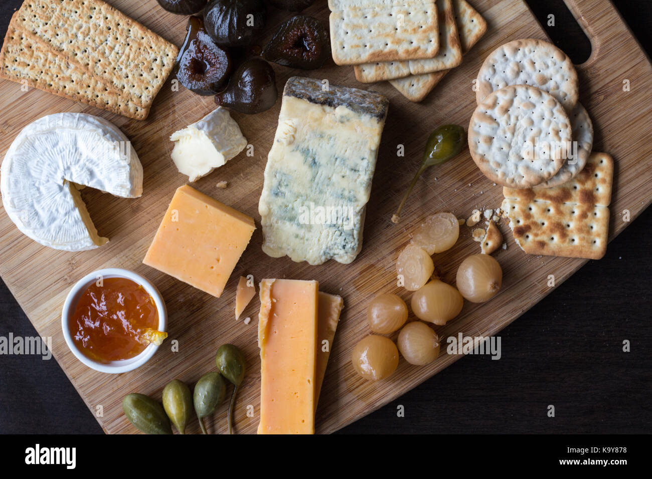 Cheese board serving with figs, caper berries, jam and pickled onions. Top view photograph with copy space - Stock Image