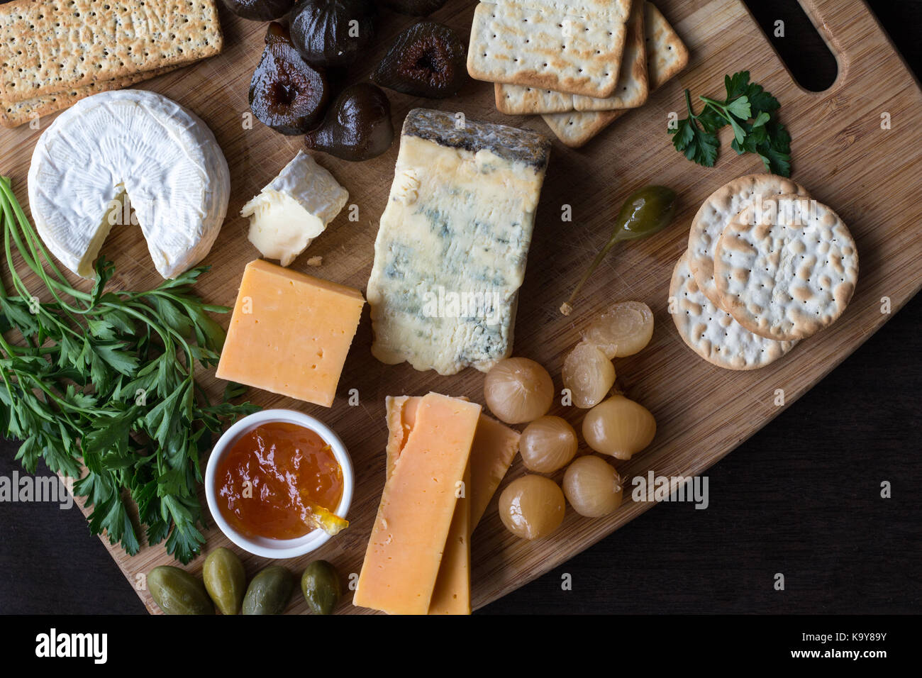Cheese board serving with figs, caper berries, jam, parsley and pickled onions. Top view photograph with copy space - Stock Image