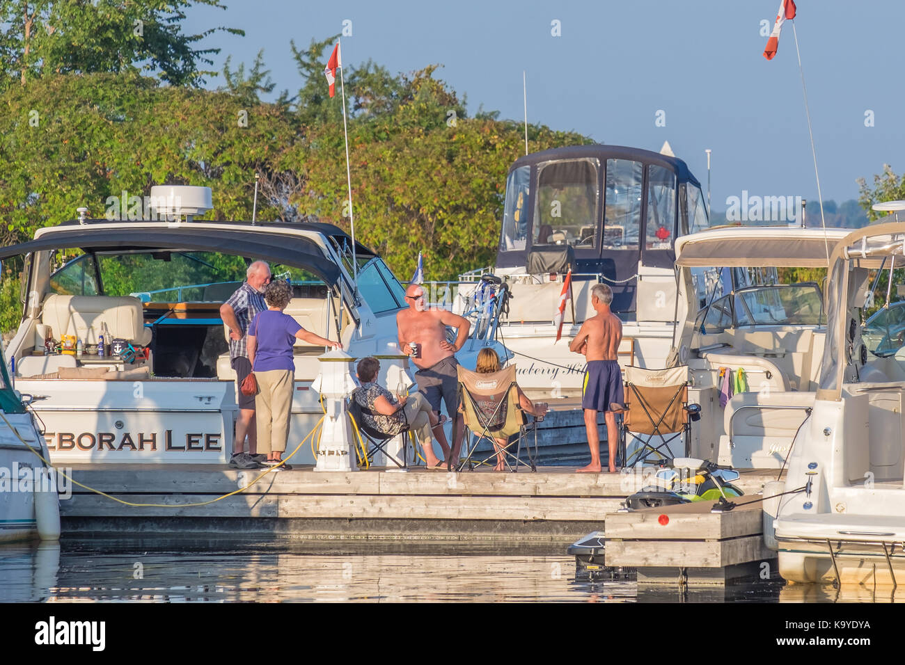 Group of boaters gather on the dock to socialize and enjoy a warm autumn evening in Orillia Ontario Canada. - Stock Image