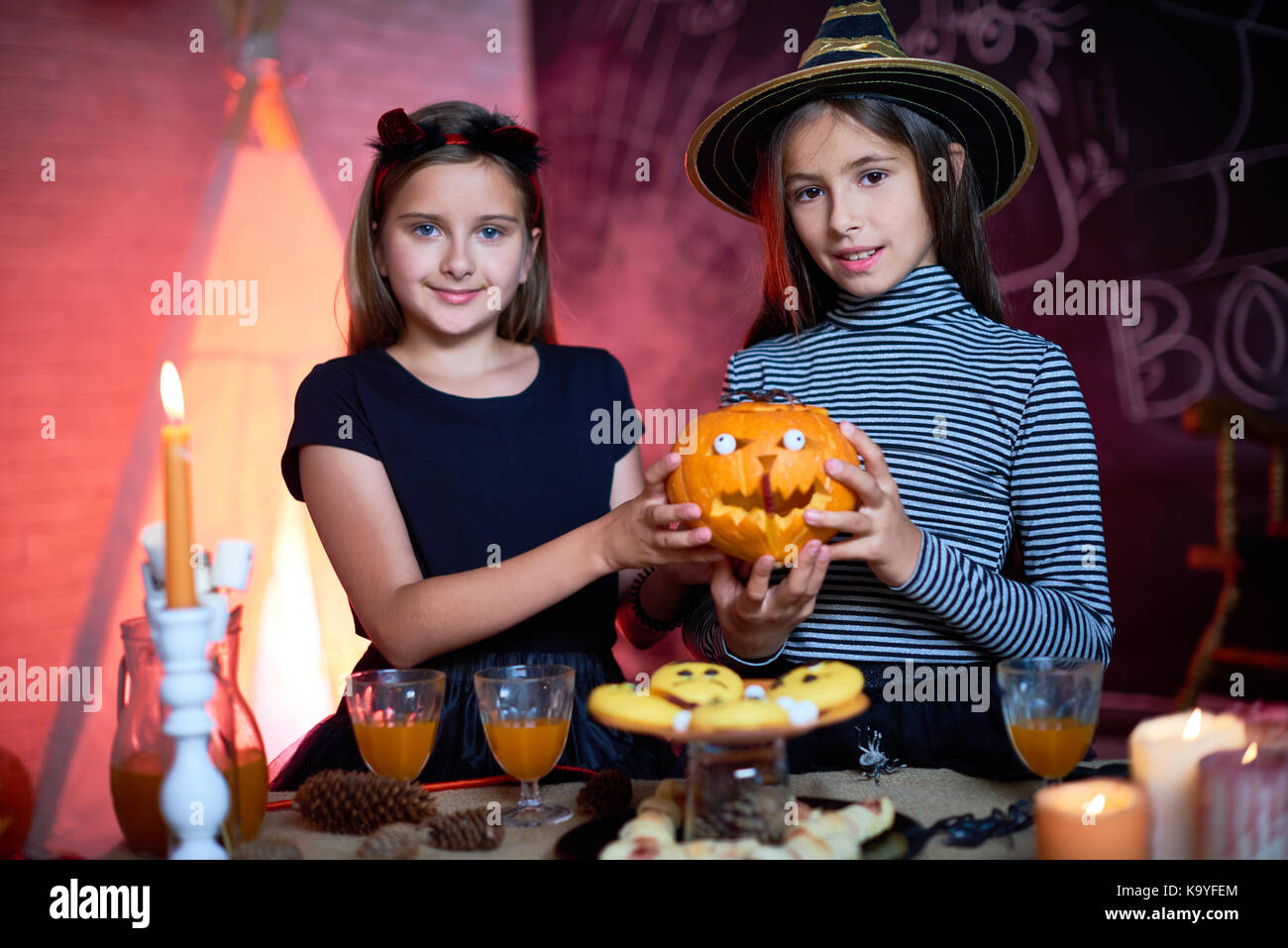Smiling pretty friends dressed as witches holding carved pumpkin with eyeballs and looking at camera near candy - Stock Image