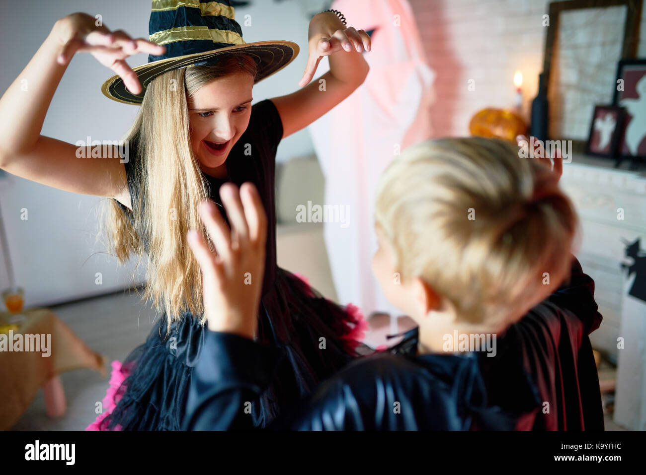 Funny emotional children in Halloween costumes doing role-playing and scaring each other imaging that they are monsters - Stock Image