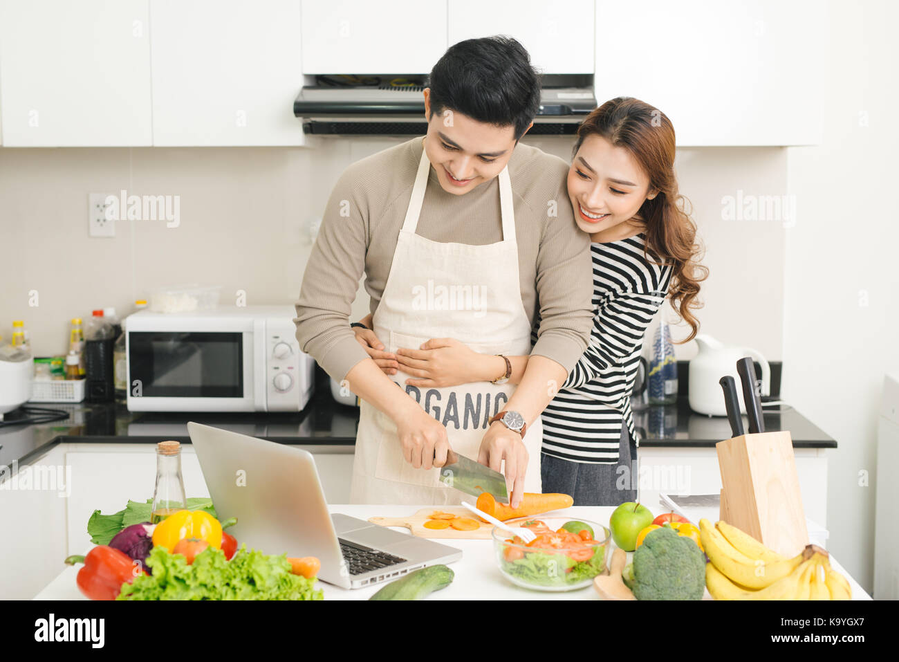 Happy asian couple watching tv show on the laptop and cooking dinner - Stock Image