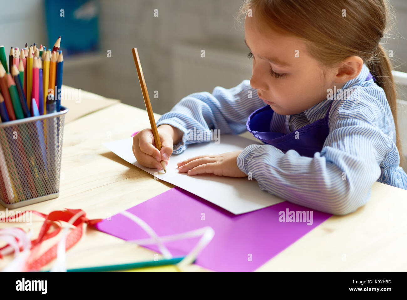 Portrait Of Cute Little Girl Drawing Picture At Desk In Art Class