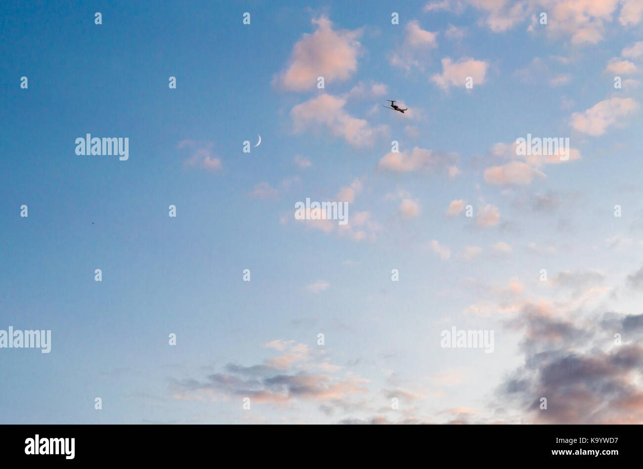 small private plane flying high in a late day sky with sliver of the moon visible, southampton, ny - Stock Image