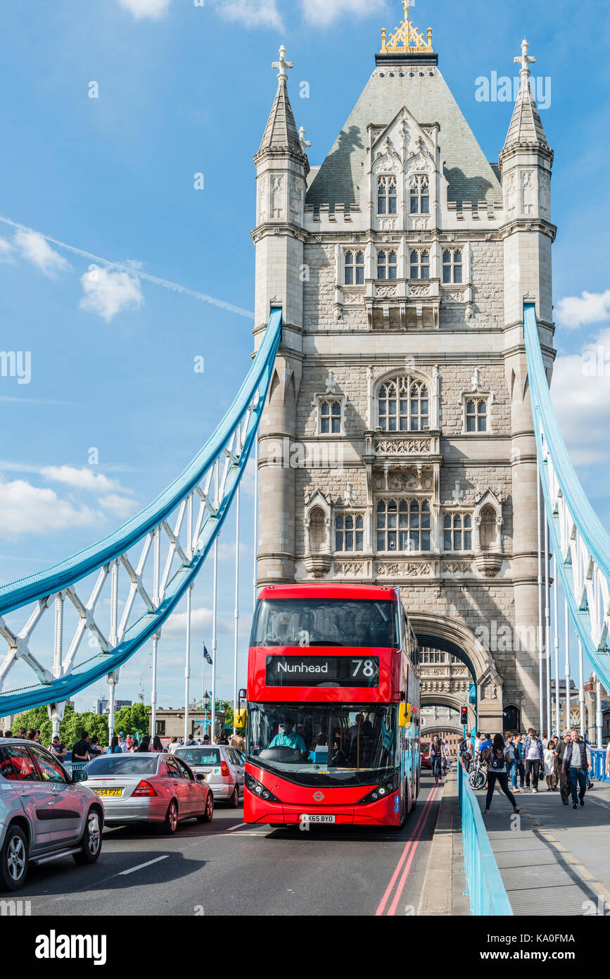 Red double-decker bus crosses Tower Bridge, London, England, United Kingdom - Stock Image