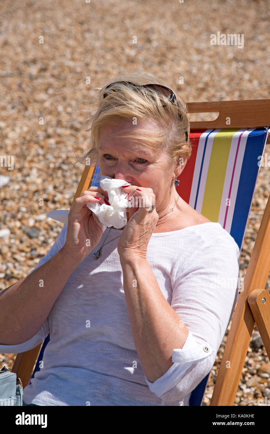 Woman sitting in a deckchair at the seaside suffering from a runny nose. Blowing her nose - Stock Image
