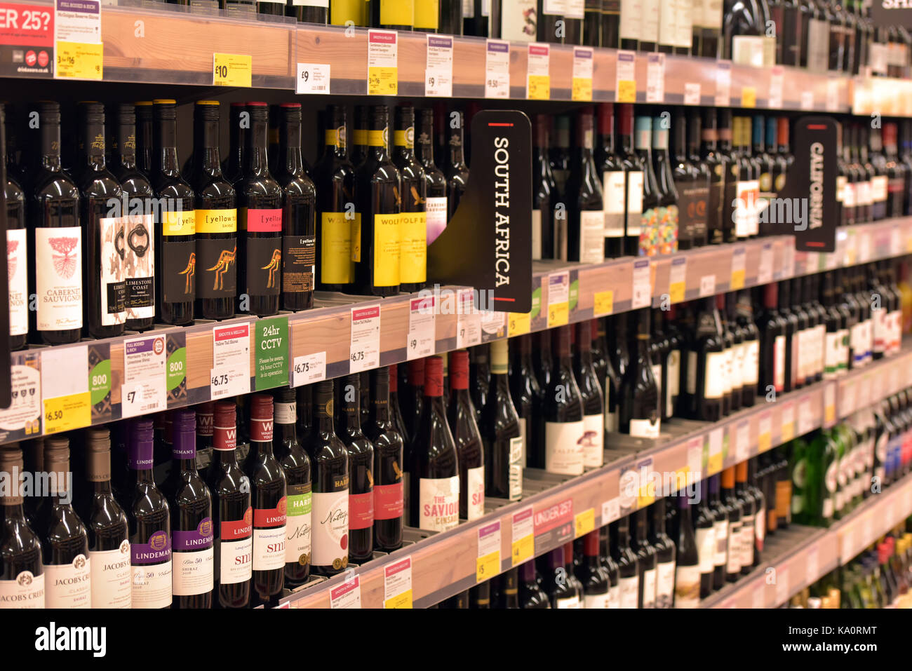 Bottles of wine for sale in a supermarket. Shelves full of red and white wine. - Stock Image