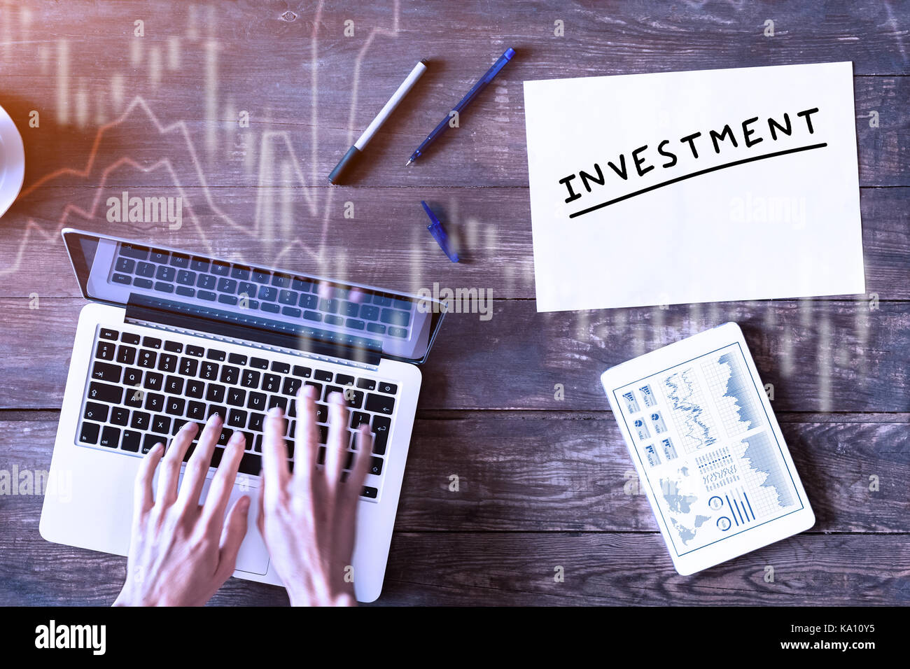 Investment concept with business person typing on computer and financial dashboard on digital tablet, top view wooden - Stock Image