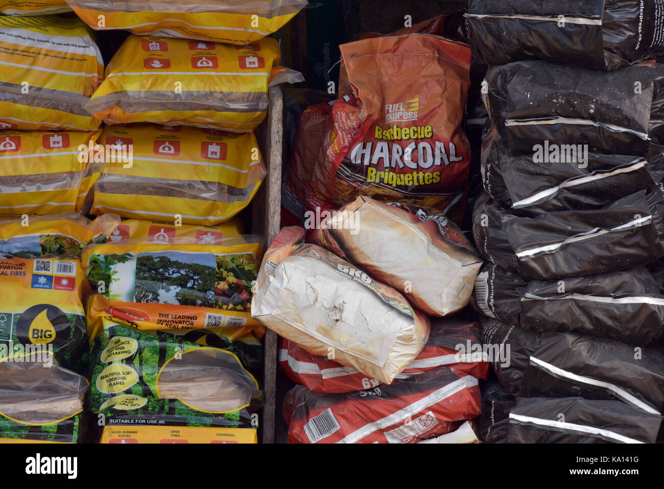 Bags of smokeless fuel and barbecue coals and briquettes in sacks stacked up ready for purchase at a shop or garden - Stock Image