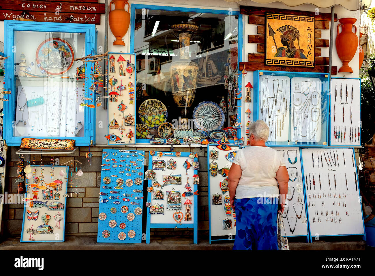 Skiathos, Greece. September 13, 2017.  A senior holidaymaker browzing the shop window of a Greek arts shop in the - Stock Image