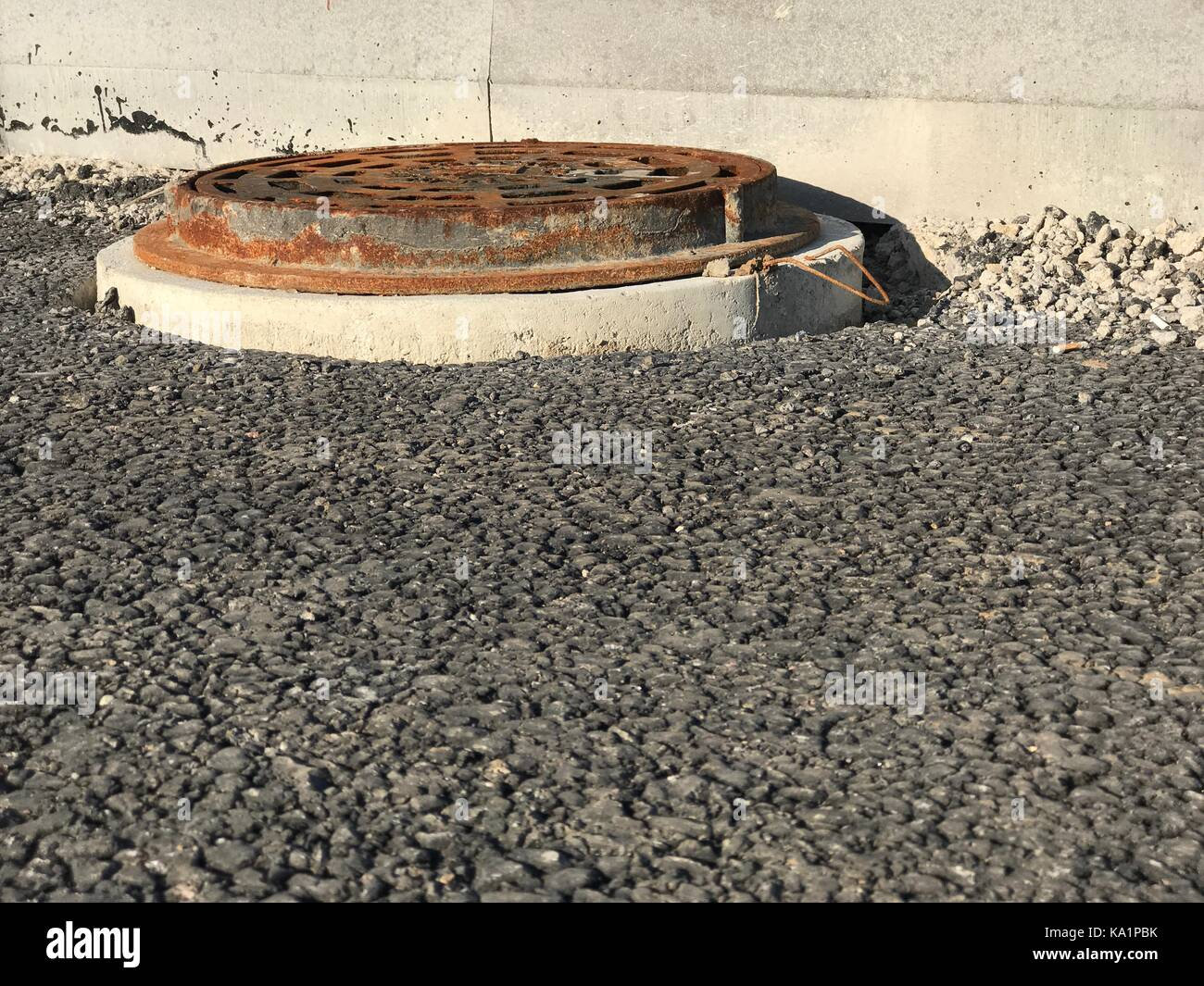 Rusty iron manhole set into asphalt road surfaces - Stock Image