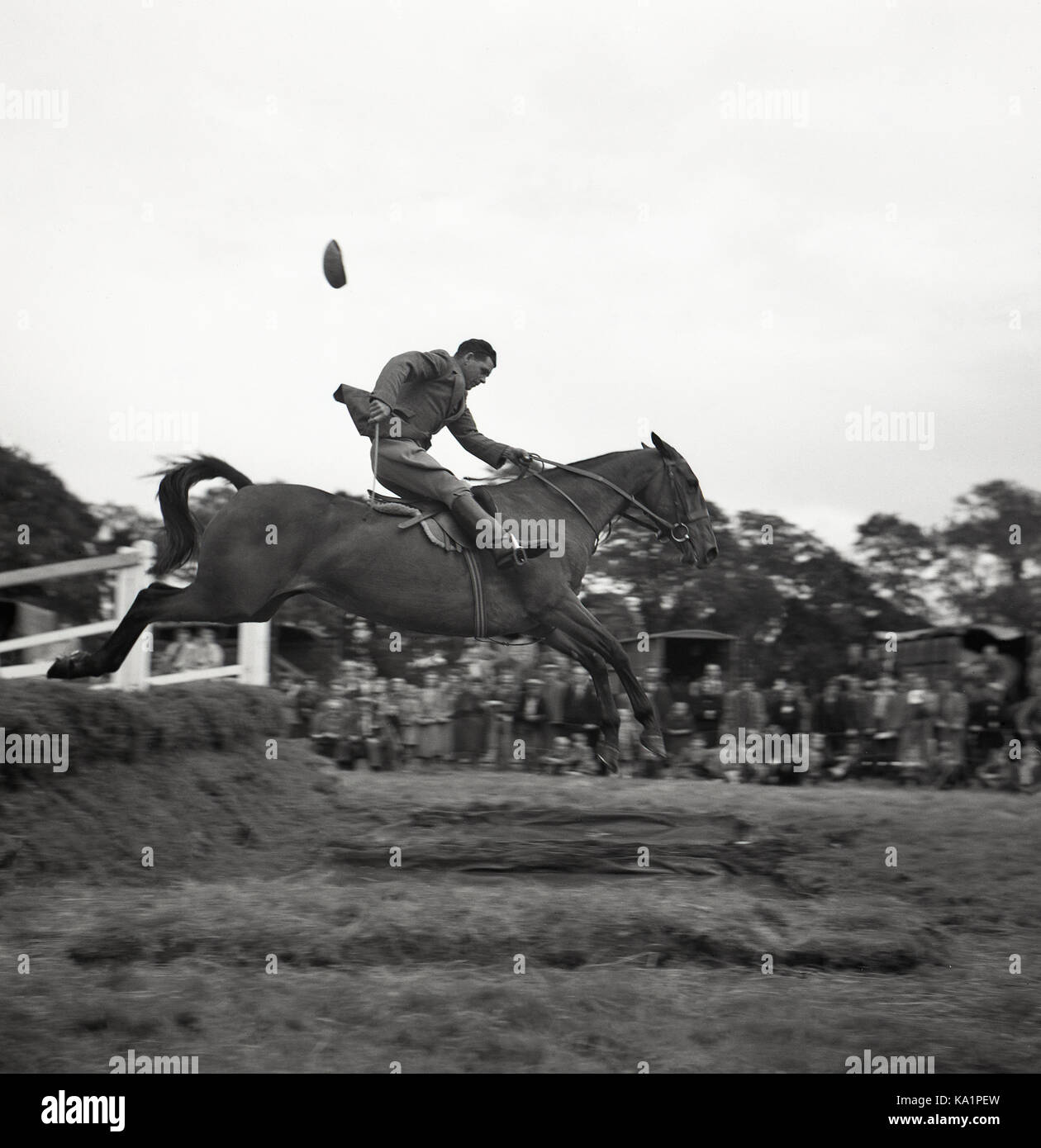1950s, historical, outdoor eventing competition, a male rider on his horse jumping over a water fence holding the - Stock Image