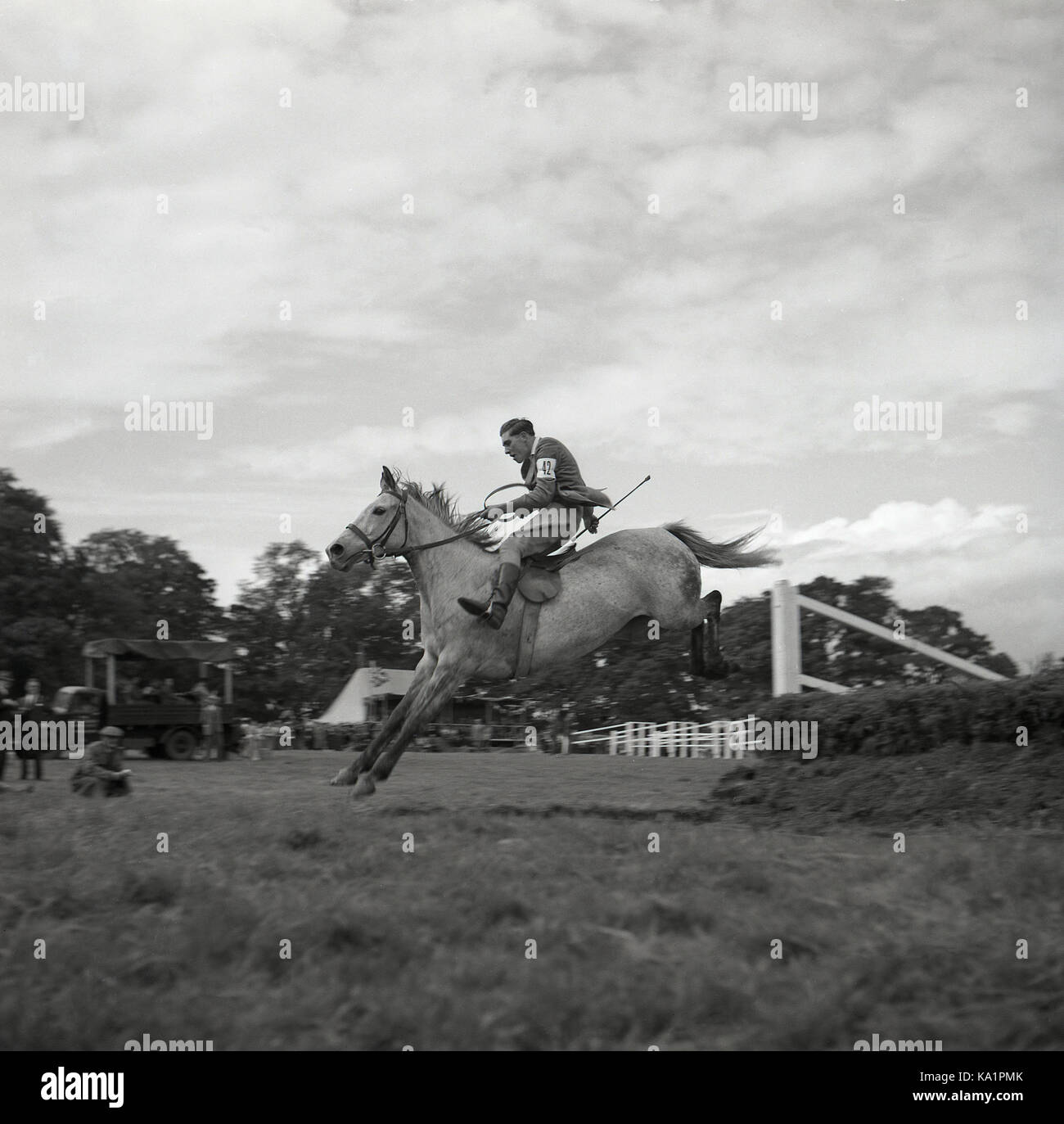 195s, historical, outdoor eventing competition, picture shows a male rider skilfully jumping over a fence on his - Stock Image