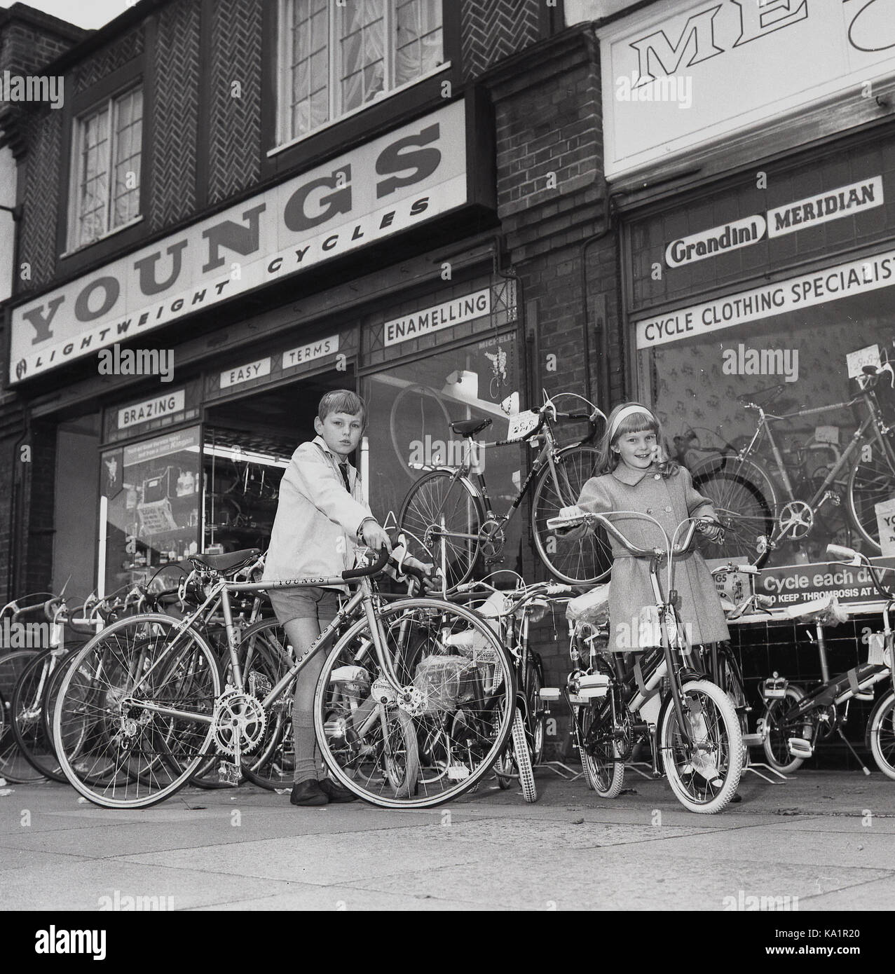 1970s, historical, an excited young boy and girl try out the bikes on display outside Youngs lightweight cycle shop, - Stock Image