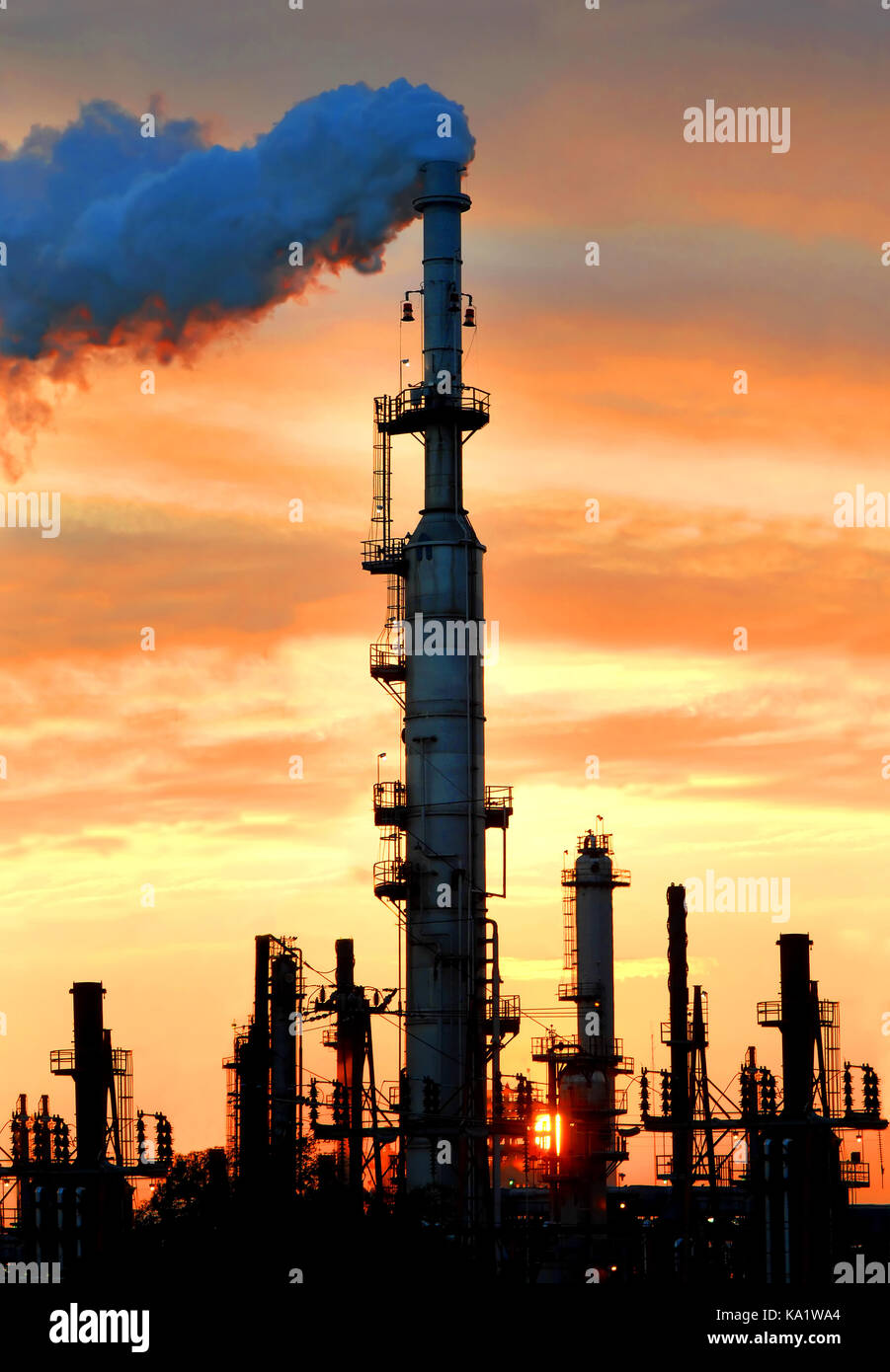 Orange tints the evening sky as the sun sets behind oil refinery smoke stack.  Steam rolls from stack as steam is - Stock Image