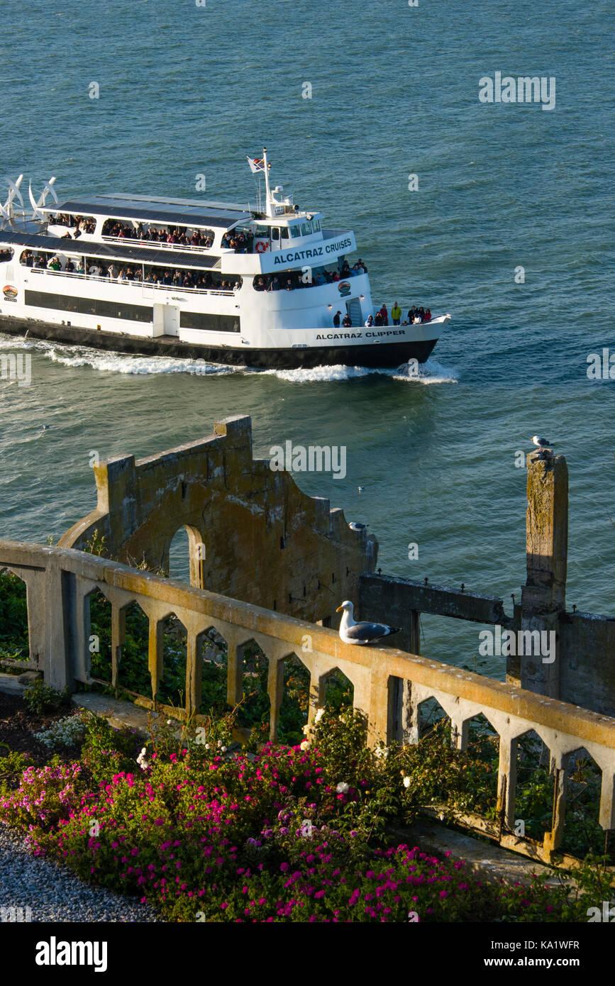 Alcatraz Cruises tour boat passing by Alcatraz Island, San Francisco Bay - Stock Image