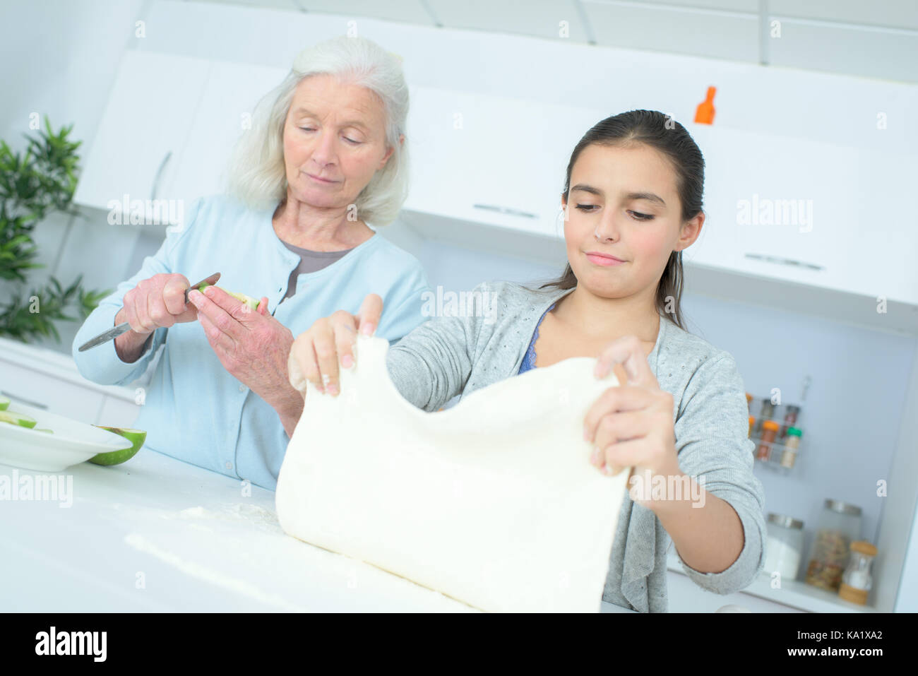 senior nanny cooking with girl - Stock Image