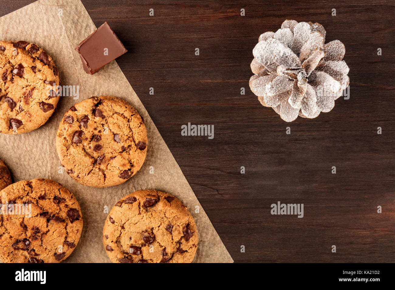 Chocolate chips cookies, snowy pine cone, copy space - Stock Image