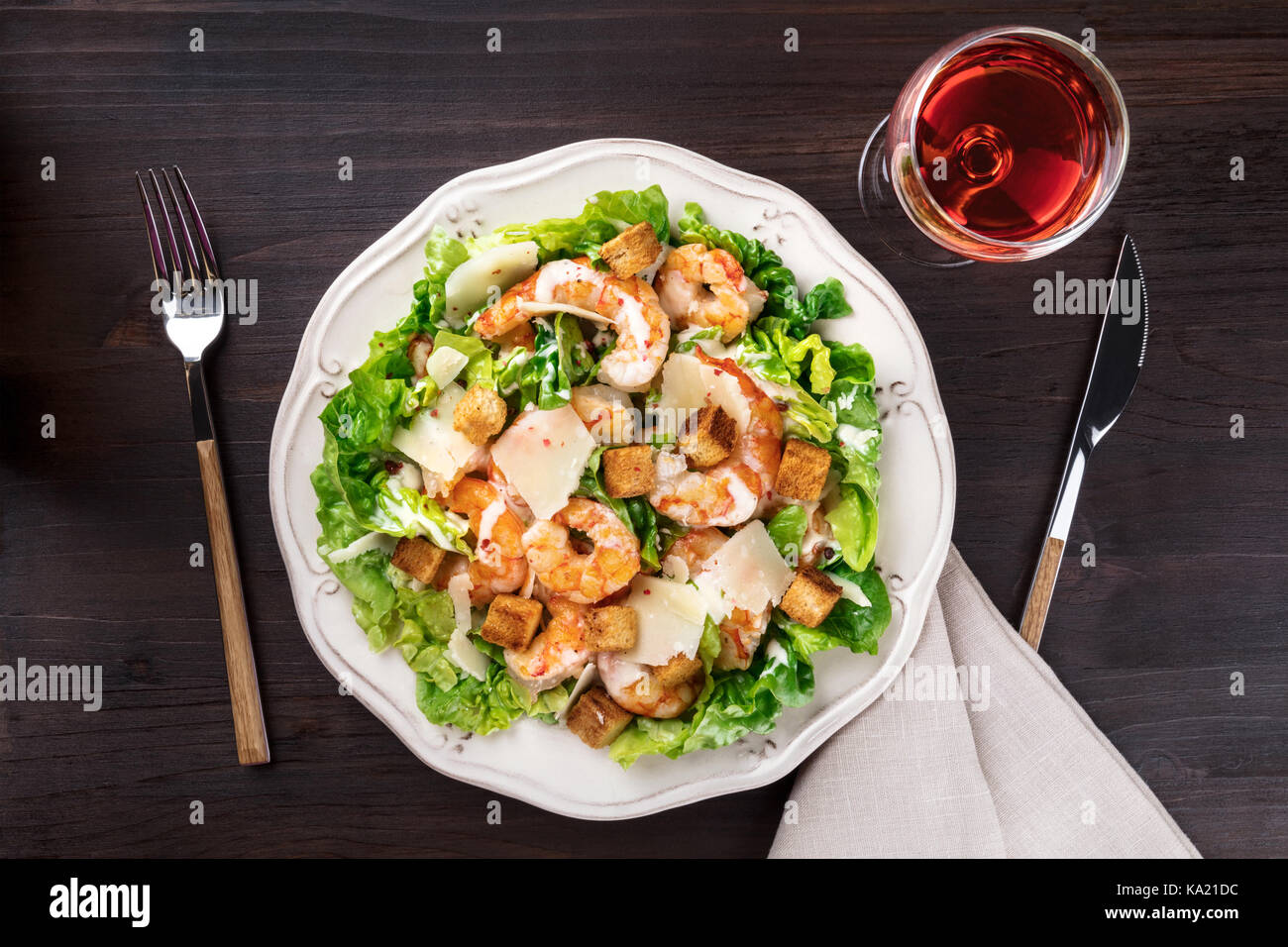 Overhead photo of shrimp Caesar salad with rose wine - Stock Image