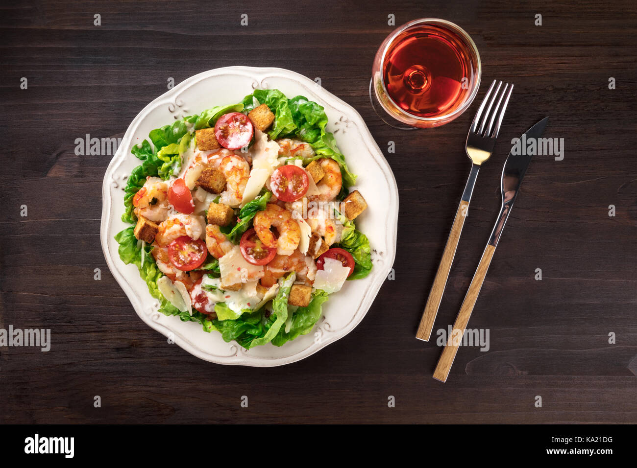 Overhead photo of shrimp Caesar salad with wine glass - Stock Image
