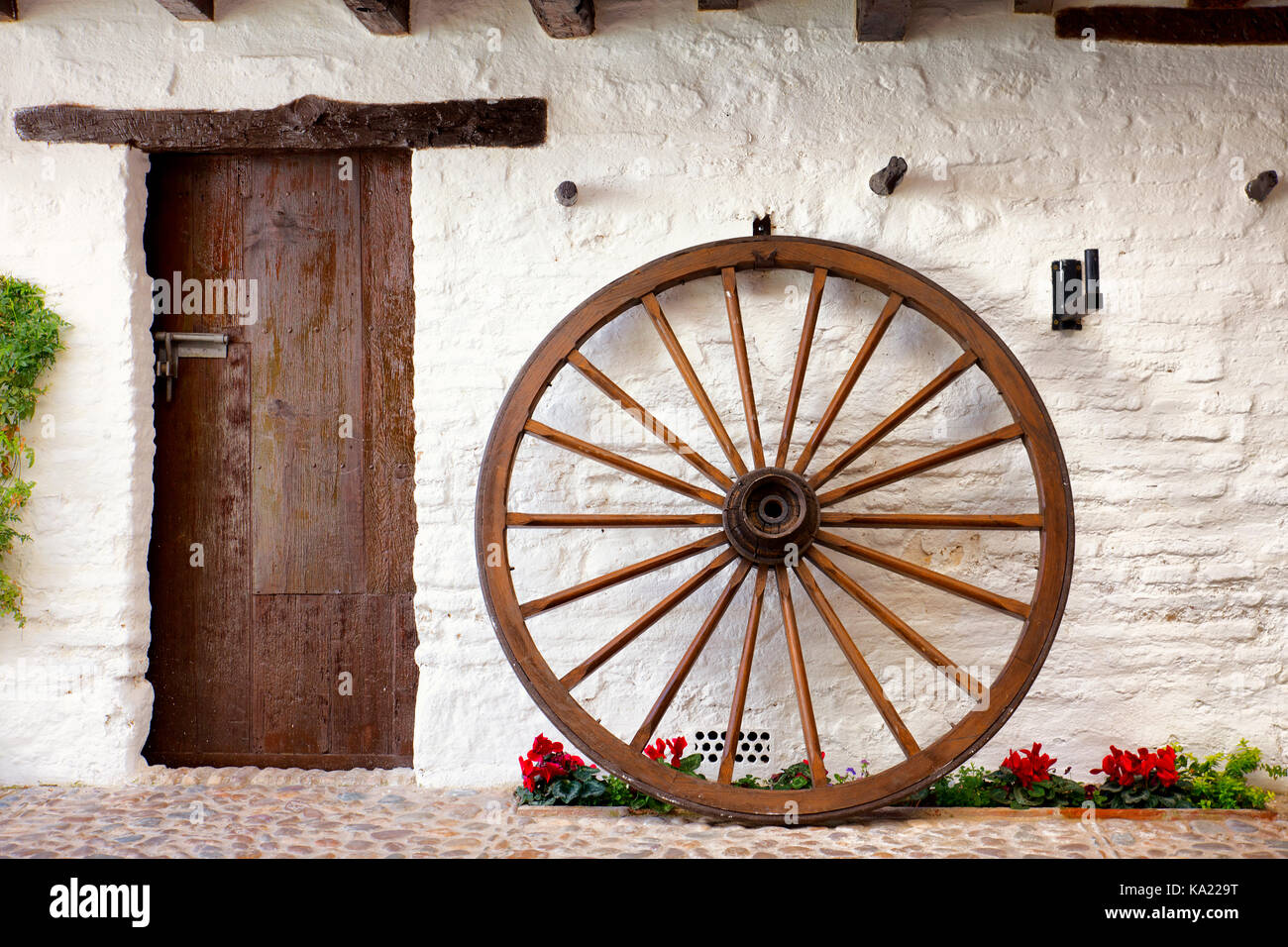 wooden cartwheel and rustic door in typical andalusian patio. Cordoba, Spain - Stock Image
