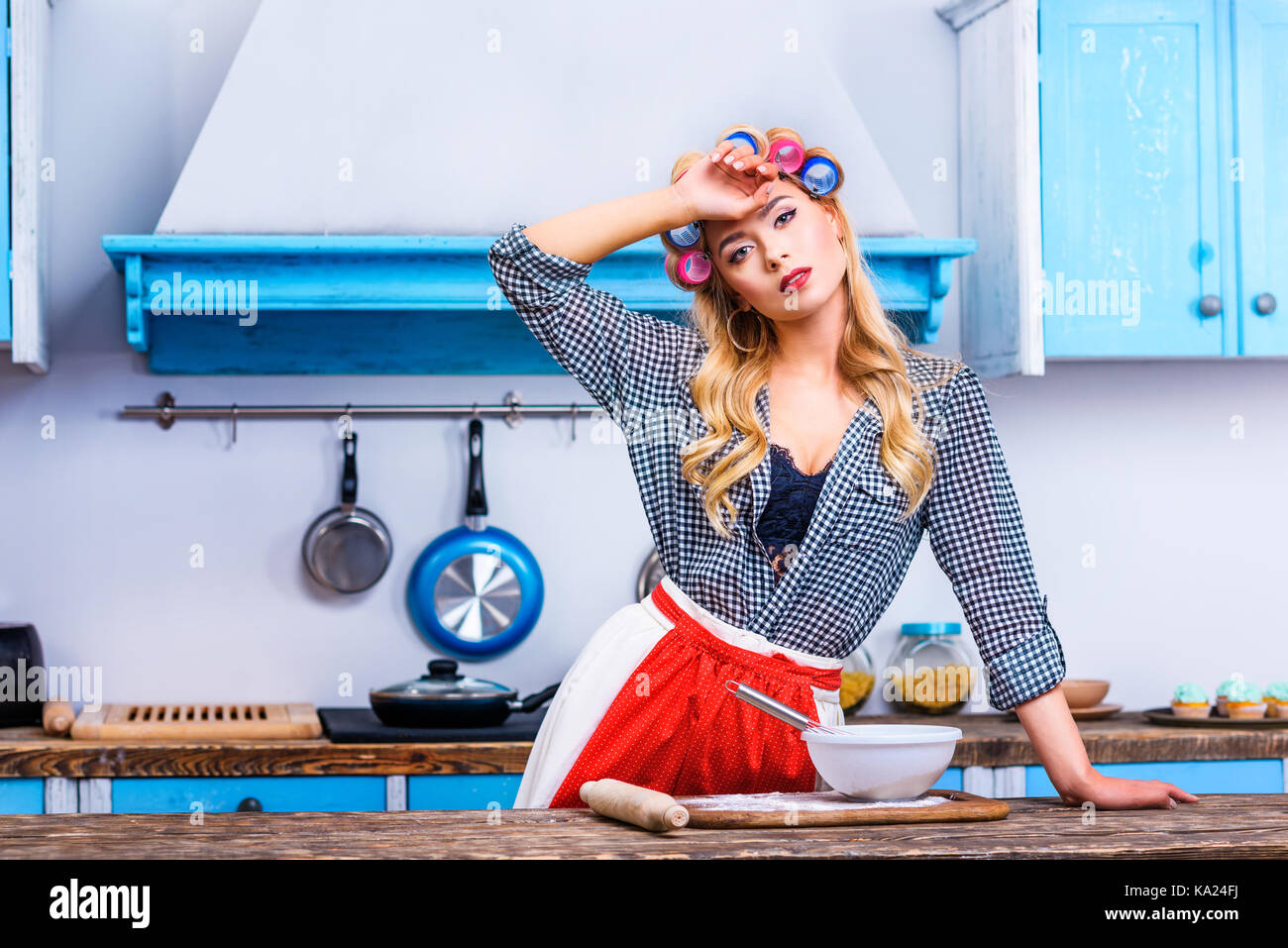 tired housewife cooking in kitchen - Stock Image