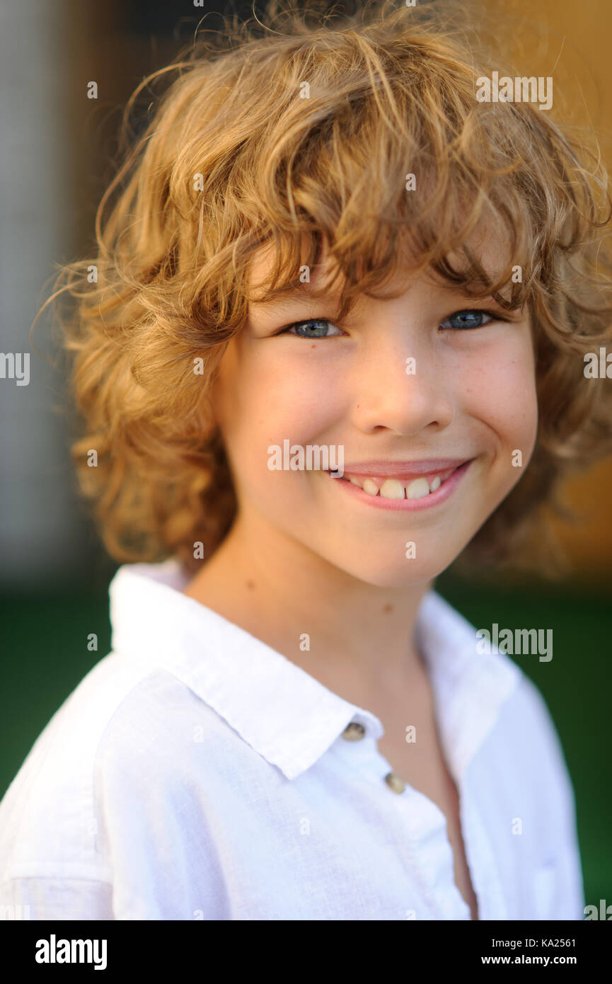 Portrait of the nice boy of 10-11 years. The fellow has beautiful fair curly hair, blue cheerful eyes, suntanned - Stock Image