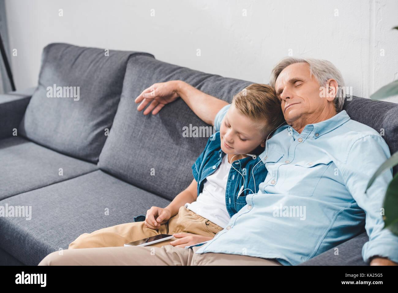 grandfather and grandson sleeping on sofa - Stock Image