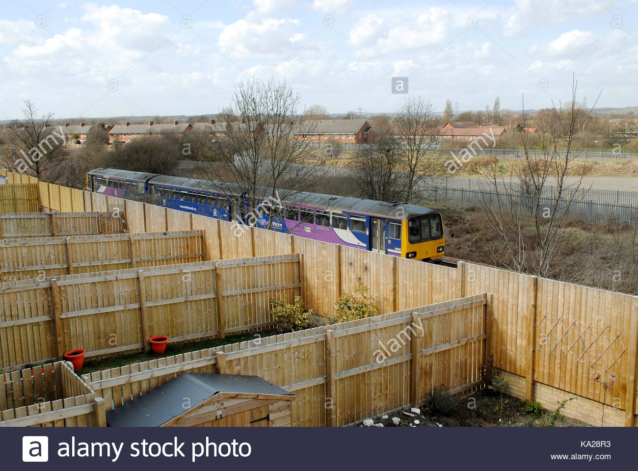 A class 144 DMU on Northern Rail passes close to urban gardens on the Leeds to Castleford railway line in West Yorkshire. - Stock Image