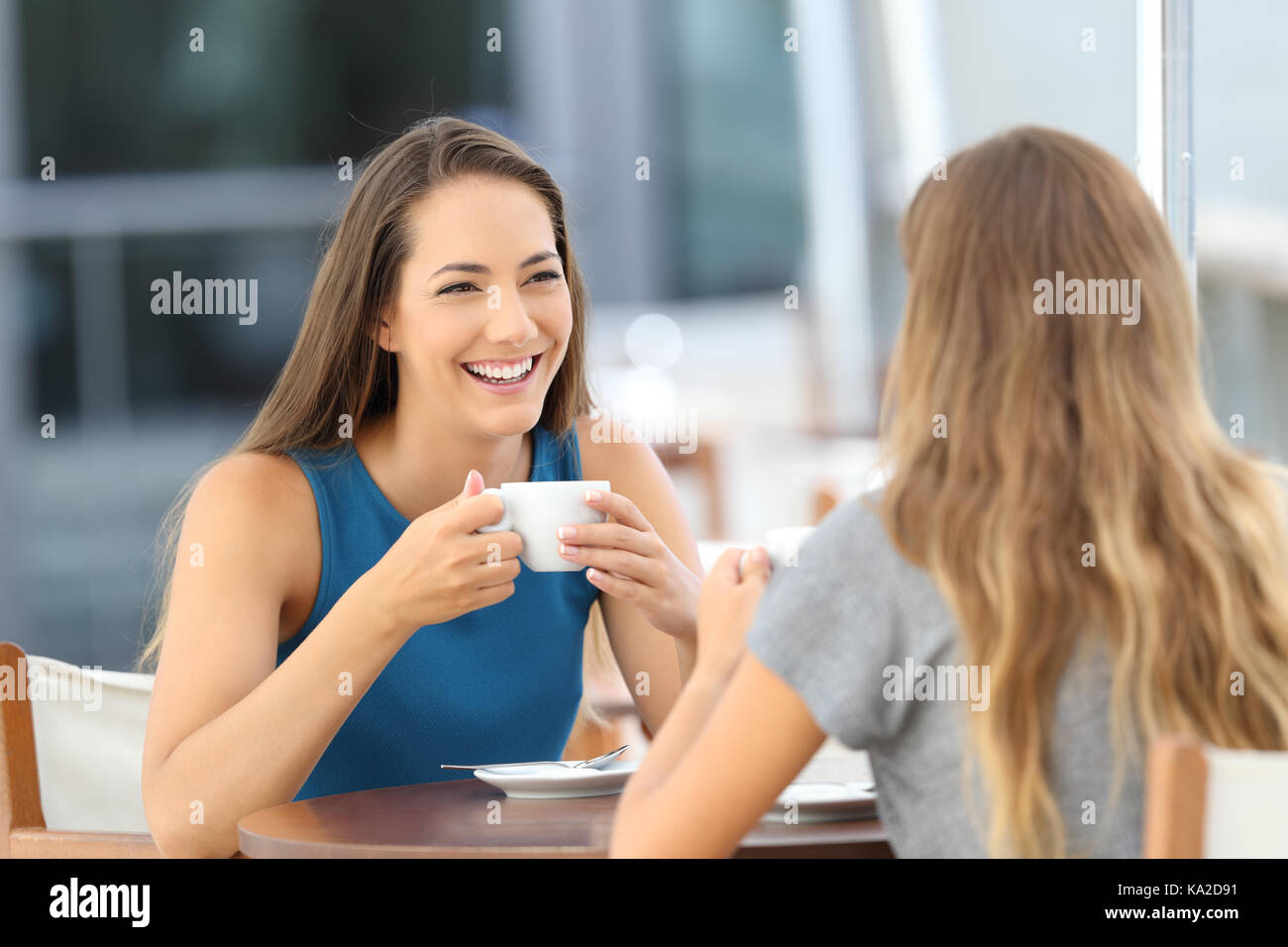 Two happy friends having a casual conversation sitting in a bar terrace - Stock Image