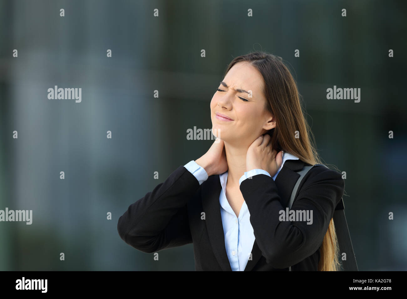 Executive suffering neck ache standing alone on the street - Stock Image