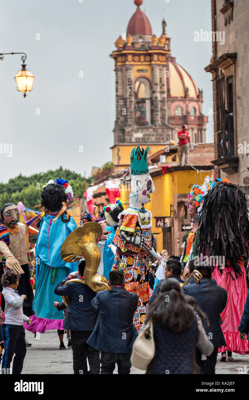 A parade of giant paper-mache puppets called mojigangas dance in a procession through the city at the start of the - Stock Image