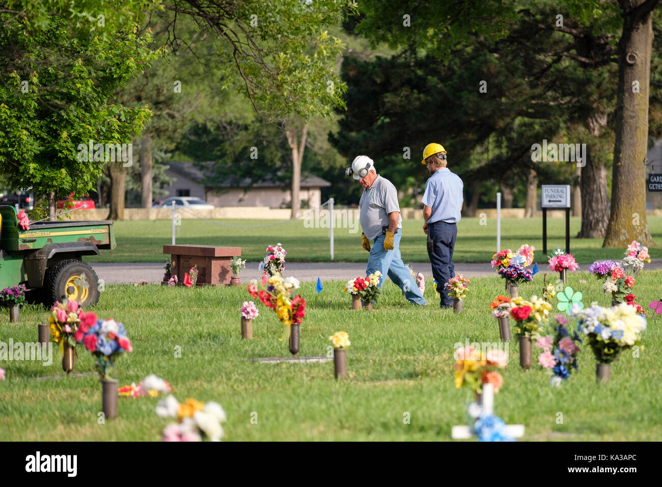 Two cemetery employees walk among floral decorations honoring the dead on Memorial Day in a cemetary in Wichita, - Stock Image