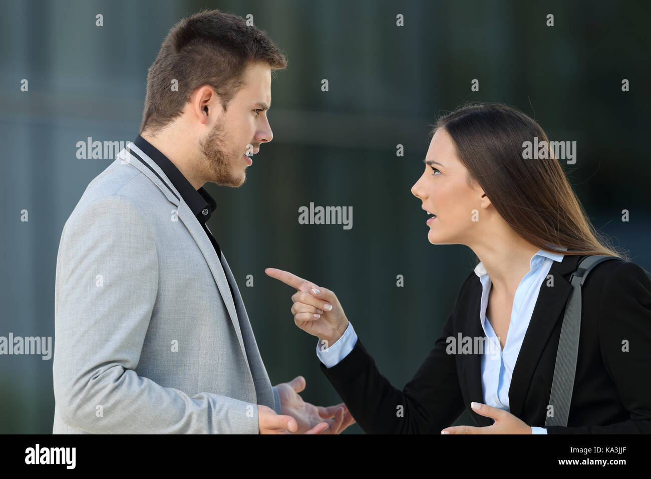Side view of an angry couple of executives arguing standing on the street - Stock Image