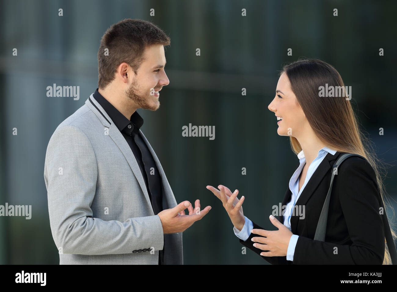 Side view portrait of a happy couple of executives talking on the street - Stock Image