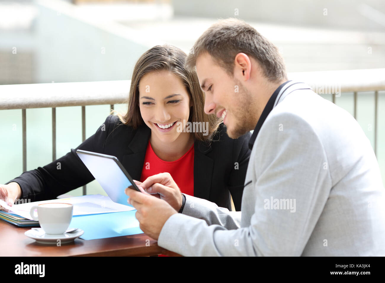 Two executives consulting on line data in a tablet sitting in a restaurant terrace - Stock Image